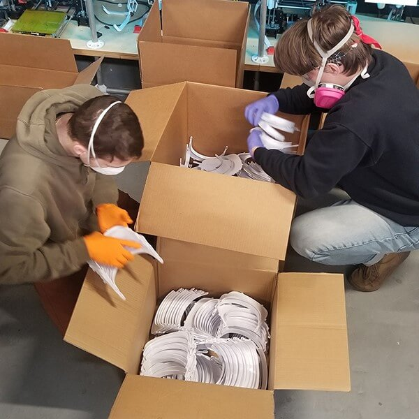 2 volunteers packing up face shields to send to hospitals